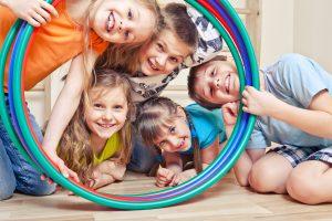 fünf Kinder, die durch bunte Reifen schauen